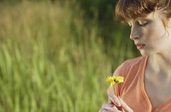 Profile of red haired woman looking at yellow flower Stock Photos