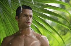 Man under giant leaf in rain shower Kuvituskuvat