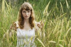 Red haired woman standing in tall grass Stock Photos