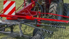 Massive rotary hay rake lifts up Stock Footage