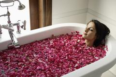 Woman in tub with floating petals Stock Photos