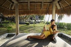 Young couple sitting under thatch cabana Stock Photos