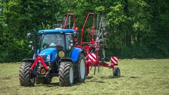 Blue tractor driving very fast across the mowed lawn Stock Footage