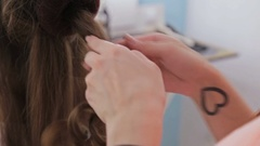 Close up shot. Hairdresser doing hairstyle for young pretty woman - top knot Stock Footage