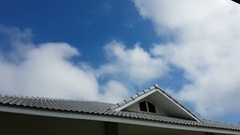 Time lapse clouds passing over house gables, Thailand Stock Footage