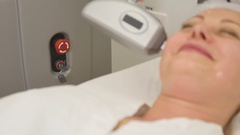 Picture of pretty beautician doing rf-lifting procedure for woman laying down in Stock Footage