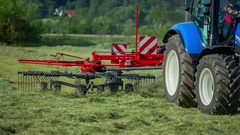 Red machinery for raking hay Stock Footage