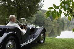 Senior man looking at lake from antique car Stock Photos