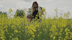 Young pregnant woman with long hair with a little girl going on flowering rapese Stock Footage