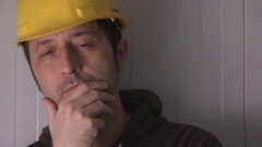 Thoughtful construction worker with protective yellow helmet Stock Footage
