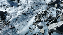 Tilt from Melting snow to the glacier and snowy mountains Stock Footage