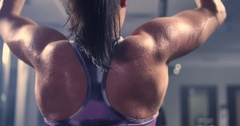 Girl doing exercise on the back muscles in a block simulator Stock Footage