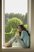 India, Young woman sitting on window sill and talking on mobile phone Stock Photos