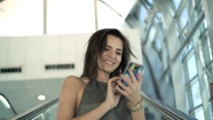 Young woman using smartphone riding on the escalator stairs Stock Footage