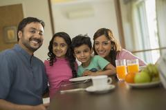 Family of four at dining table Stock Photos