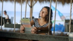 Brunette in a striped blouse with bare shoulders sitting at the bar and rest Stock Footage