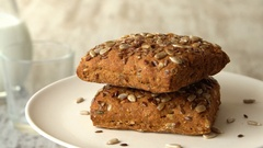 Two delicious homemade small loafs of bread with seeds. Milk-jug, on wooden Stock Footage