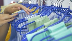 Girl seek cloth on demonstration stand in showroom Stock Footage
