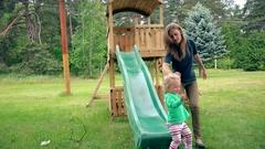 Babysitter woman help toddler child to slide down in playground Stock Footage