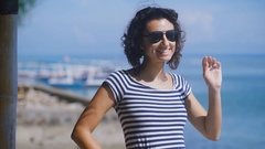 Close up of a beautiful brunette with short frizzy hair with blue sea in the Stock Footage