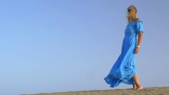 Slow motion view of young blond woman standing against blue sky in long blue Stock Footage