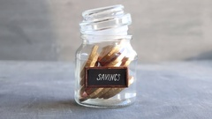 Coins in glass money jar with savings label, financial idea Stock Footage