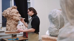 Sculptor modelling sculpture adjusting face details head made of clay Stock Footage