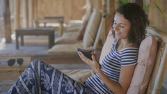 Cute tanned girl in a striped T-shirt and blue pants sitting outdoor on a chair Stock Footage