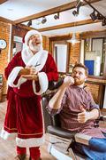 Santa claus as master at barber shop Stock Photos