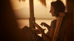 Sunset and beach on the island of Bali. The girl in a striped blouse and wide Stock Footage