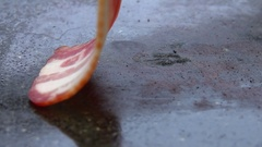 Close-up of a slice of bacon lays on the grill Stock Footage