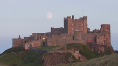 Rising Moon behind Bamburgh Castle Northumberland Stock Footage
