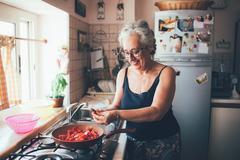 Woman chopping tomatoes into saucepan smiling Stock Photos