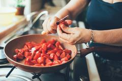 Cropped view of woman chopping tomatoes into saucepan Stock Photos