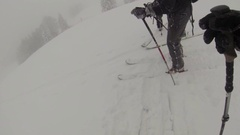 Group of people downhill skiing in a whiteout on a snow covered mountain. Stock Footage