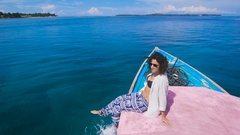 The girl on the island of Bali tours. She sits on the edge of the boat, admiring Stock Footage