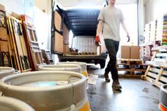 Worker in brewery, preparing to distribute barrels of beer Stock Photos
