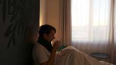 Sad sick man in a bed under the blanket drinking hot beverage Stock Footage