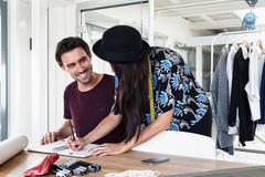 Colleagues sketching fashion design, smiling Stock Photos