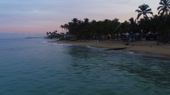 Beach in the evening, the sea, palm trees, sand, people far away Stock Footage
