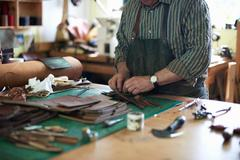 Male worker in leather workshop, arranging leather, mid section Stock Photos