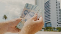 Man recounts Vietnamese money. Five hundred thousandth bills in the background Stock Footage