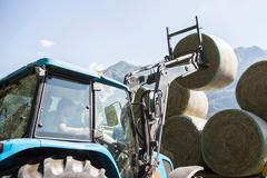 Harvesting tractor stacking circular haystacks Stock Photos