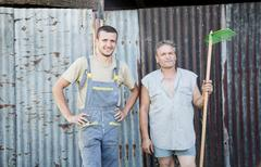Portrait of two male farmworkers in farmyard Stock Photos