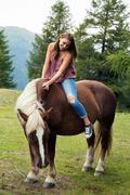Young woman sitting on palomino horse, Sattelbergalm, Tyrol, Austria Stock Photos