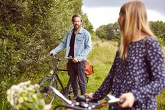 Female cyclist looking back at boyfriend on rural path Stock Photos