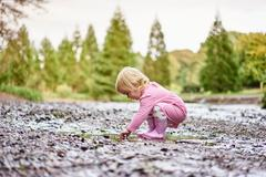 Baby girl wearing rubber boots playing in muddy puddle Stock Photos