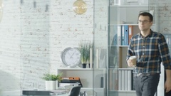 Man Walking into an Office and Sipping Coffee Sits at His Workplace.  Stock Footage