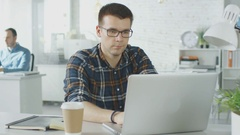 Face Front Man Sitting at His Creative Office Table Working on His Laptop.  Stock Footage