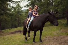 Girl and woman sitting bareback on horse in forest glade, Sattelbergalm, Tyrol, Stock Photos